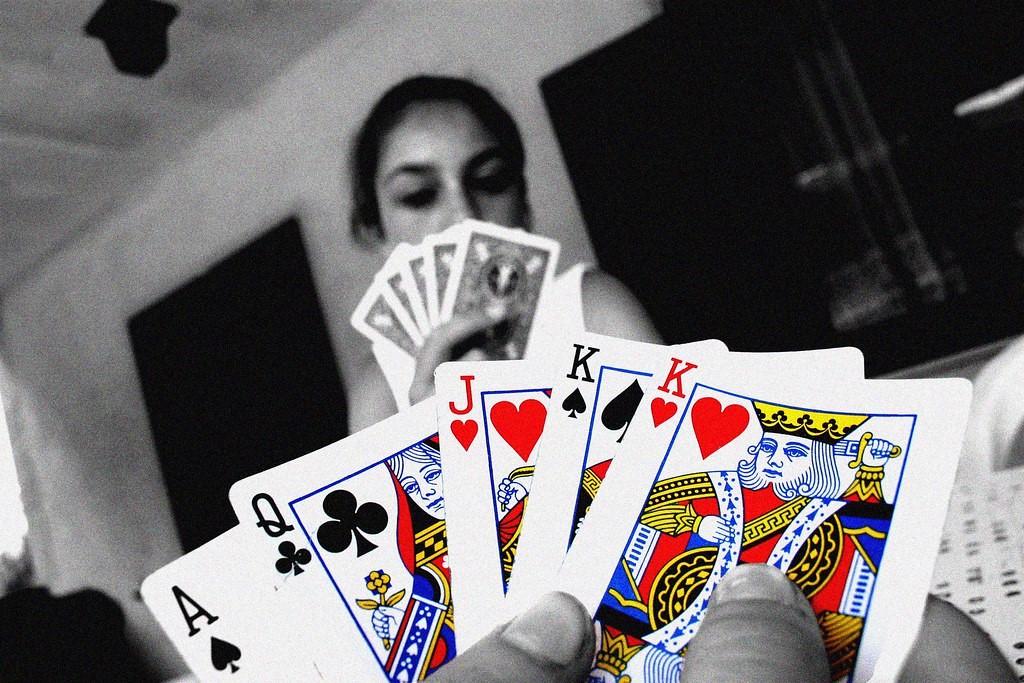 To poker spillere der holder deres kort. En med bagsiden ud og en fra forsiden.